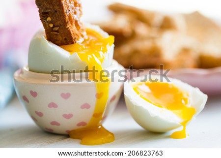 Series on boiled duck egg for breakfast, with toast soldiers - stock photo