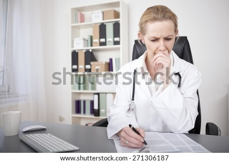 Serious Adult Female Medical Doctor Reading Medical Documents on the Table with One Hand on her Face and the Other is Holding a Pen. - stock photo