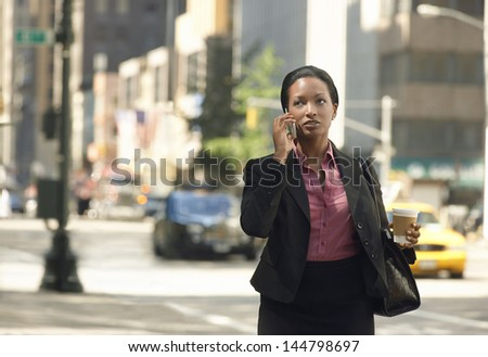 Serious African American businesswoman using mobile phone on street - stock photo