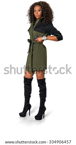 Serious African woman with medium dark brown hair in casual outfit holding handgun - Isolated - stock photo