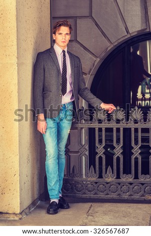 Serious American businessman in New York. Wearing blazer, necktie, jeans, leather shoes, a young college student standing by railing on balcony outside, waiting for you. Instagram filtered effect.  - stock photo