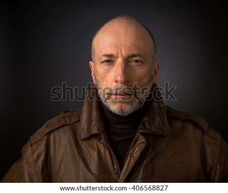serious and focused senior man in leather jacket - a headshot against a black background - stock photo