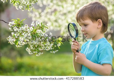 Serious and smiling cute kid guy exploring the environment with a magnifying glass - stock photo