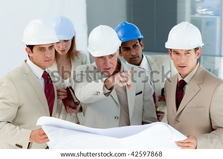 Serious architect looking at blueprints and pointing in a building - stock photo
