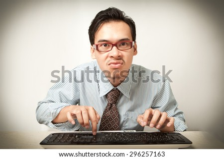 serious asian business man browsing with keyboard. - stock photo