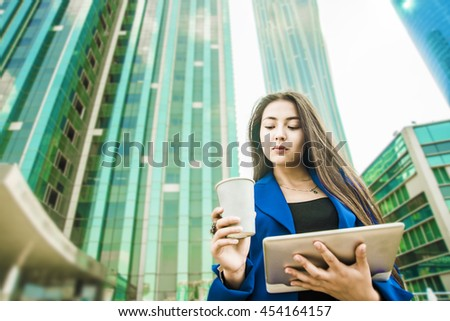 Serious asian young businesswoman with a disposable coffee cup, drinking coffee, and holding tablet in her hands against urban city skyscraper background  - stock photo