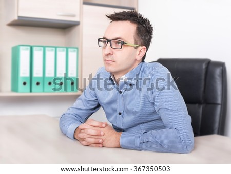 Serious attentive informal young businessman with fingers crossed sitting and listening colleagues - stock photo