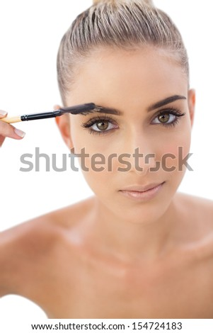 Serious attractive woman applying make up on her eyebrows on white background - stock photo