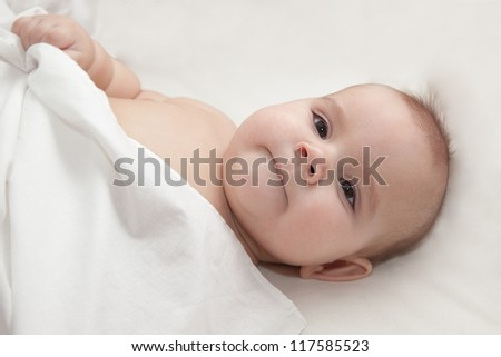 Serious baby covered with white blanket laying on white sheets in bed. Selective focus on baby face - stock photo