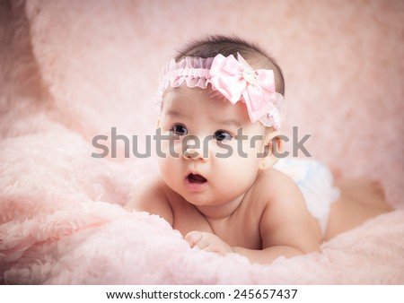 Serious baby girl looking at camera lying on pink background. Portrait of a little beautiful baby - stock photo
