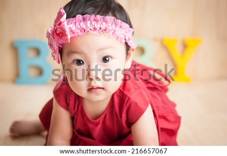 Serious baby girl looking at camera. Wearing red dress with BABY wood letter on background. Gender concept - stock photo