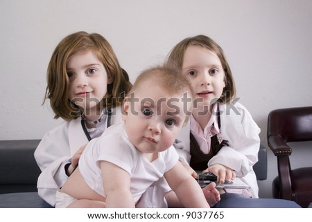 Serious baby with her sisters in a medical office. - stock photo