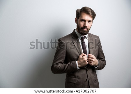 Serious bearded businessperson in suit standing against light grey. Mock up - stock photo