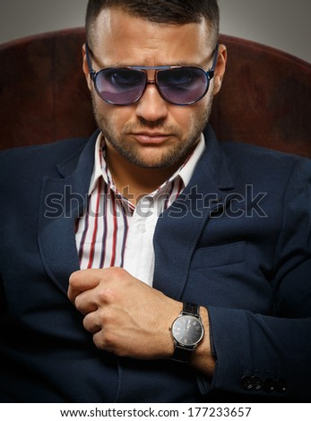 Serious bearded man wearing violet sunglasses - stock photo