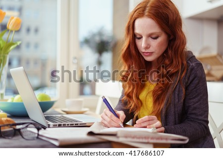 Serious beautiful young adult woman with red hair taking notes while sitting in front of laptop computer on kitchen table near window - stock photo