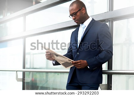 Serious Black American Businessman Reading a Newspaper at the Side of Walkway While Leaning his Back Against the Metal Railing. - stock photo