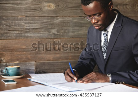 Serious black corporate worker in formal suit and spectacles signing a lucrative contract with concentrated expression while having morning cappuccino at a cafe, sitting against wooden wall background - stock photo
