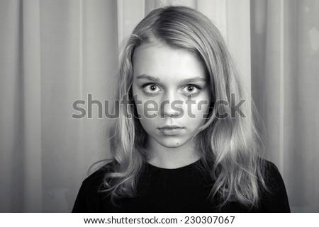 Serious blond Caucasian girl, monochrome studio portrait - stock photo