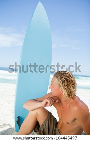Serious blonde man sitting in front of the sea next to his blue surfboard - stock photo
