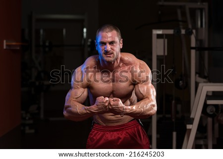 Serious Bodybuilder Standing In The Gym And Flexing Muscles - stock photo