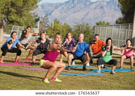 Serious boot camp exercise class squatting with weights - stock photo