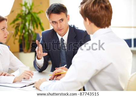 Serious boss giving some information to young office workers - stock photo