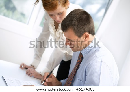 serious boss signing contract with executive secretary near by - stock photo