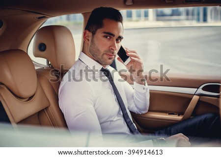Serious business man in a white shirt sits in the car. - stock photo