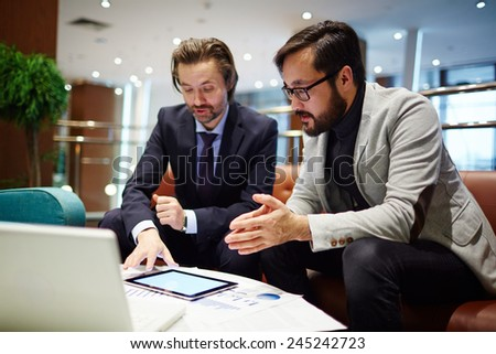 Serious business partners discussing data in touchpad - stock photo