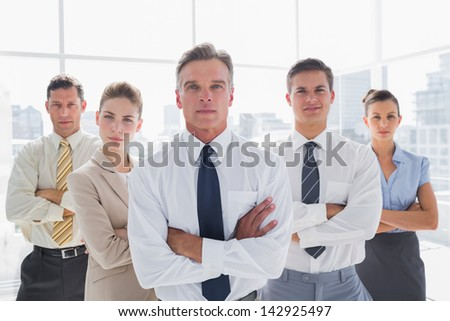 Serious business people with arms crossed in their office - stock photo