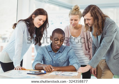 Serious business team discussing at desk in creative office - stock photo