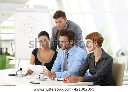 Serious business team reading papers at office meeting. Caucasian young businessman and businesswoman, suit, sitting at table, whiteboard in background. - stock photo