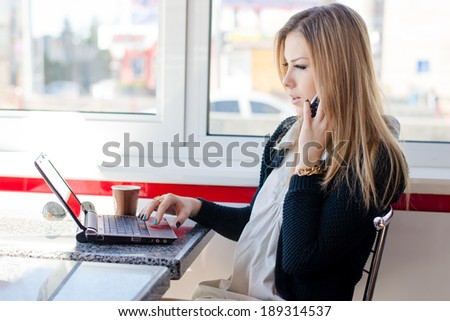 serious business woman beautiful young blond girl talking on the mobile cell phone working on a laptop pc computer sitting in a coffee shop or tea-room - stock photo