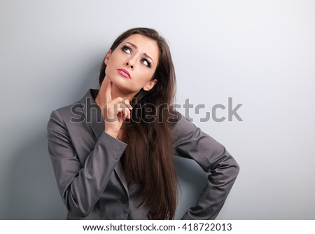 Serious business woman thinking about with finger near face and looking up on blue background - stock photo