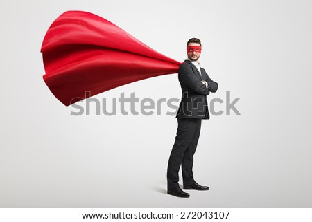 serious businessman dressed as a superhero in red mask and cloak over light grey background - stock photo