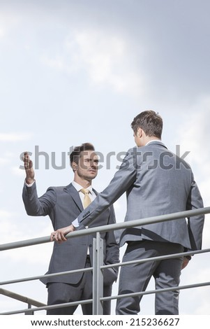 Serious businessman gesturing while looking at coworker against sky - stock photo