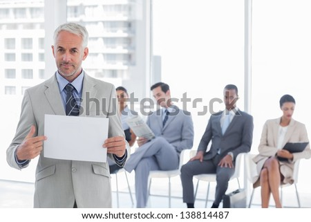 Serious businessman holding a blank notice with people waiting behind - stock photo