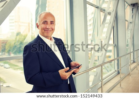 serious businessman holding tablet pc and looking at camera - stock photo