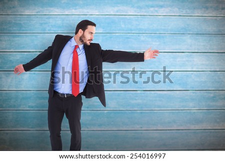 Serious businessman in suit gesturing with hand against wooden planks - stock photo
