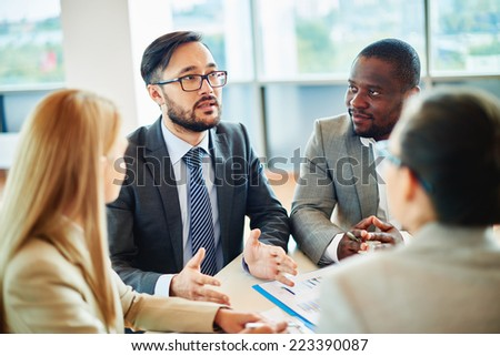 Serious businessman of Asian ethnicity speaking while his colleagues listening to him at meeting - stock photo