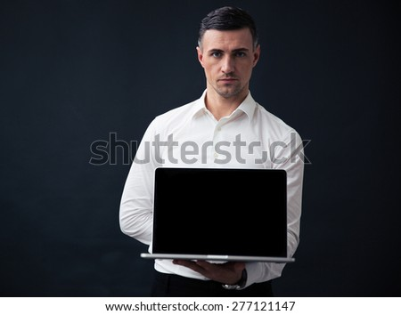 Serious businessman showing blank laptop screen over gray background. Looking at camera - stock photo