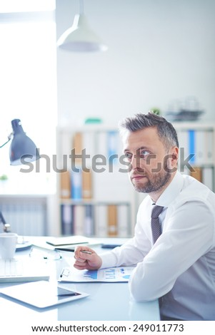 Serious businessman sitting at workplace - stock photo