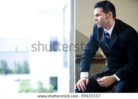 Serious businessman sitting in office looking out window - stock photo