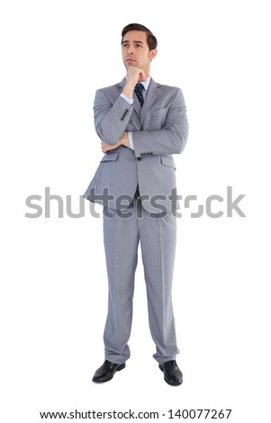 Serious businessman standing and thinking on white background - stock photo