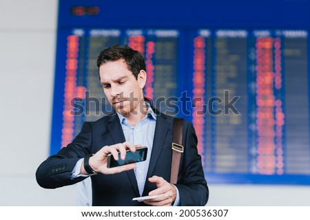 Serious businessman standing near airline schedule and looking at his watch - stock photo