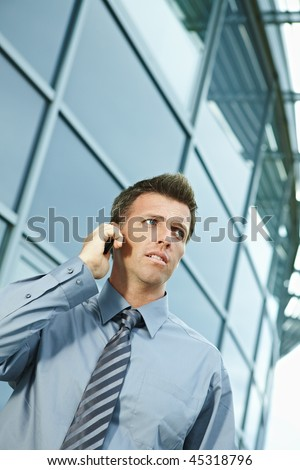 Serious businessman standing outdoor talking on mobile phone, looking away. - stock photo