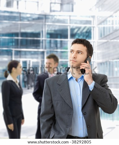 Serious businessman talking on mobile standing in office hallway. - stock photo