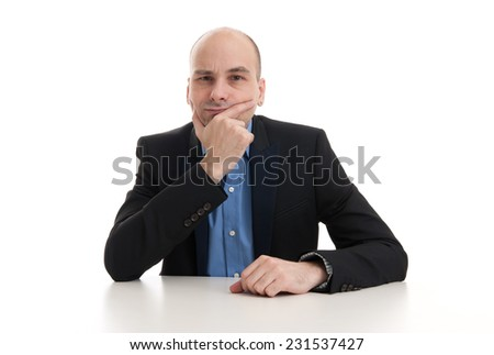 serious businessman thinking and sitting at his desk - stock photo