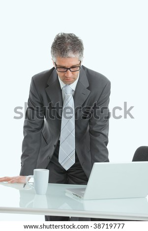 Serious businessman using laptop computer, standing behind office desk, looking down. Isolated on white. - stock photo