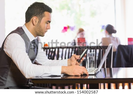 Serious businessman using phone while working on laptop in a restaurant - stock photo